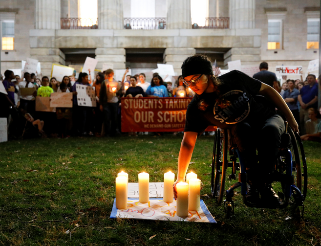 A student lights a candle in front of the North Carolina Capitol in Raleigh on Feb. 20 in memory of the victims of the shooting at Marjory Stoneman Douglas High School in Parkland, Fla. The students were calling for safer gun laws after 17 people were killed when 19-year-old former student Nikolas Cruz stormed the Parkland school on Feb. 14 with an AR-15 semi-automatic style weapon. (CNS photo/Jonathan Drake, Reuters)