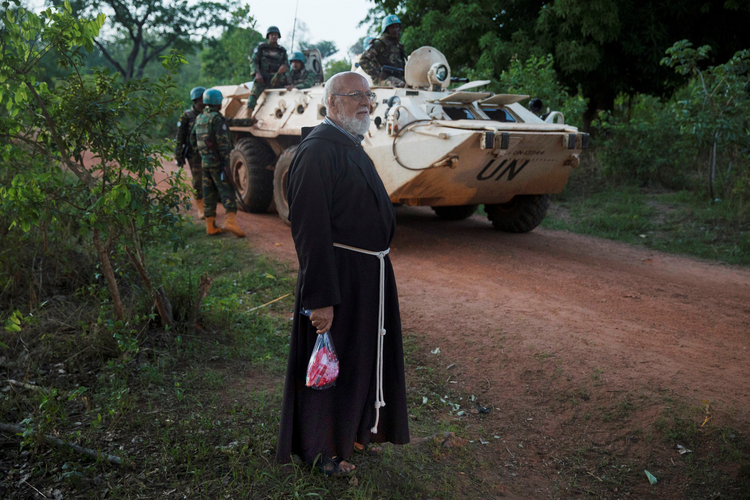 A Franciscan stands near U.N. peacekeeping soldiers in 2017 in the village of Ndim, Central African Republic. The recent death of a Catholic priest in the Central African Republic demonstrates the delicate nature of peace in the country, where a cardinal and an imam have worked to bring the population toward peace and unity. (CNS photo/Baz Ratner, Reuters)