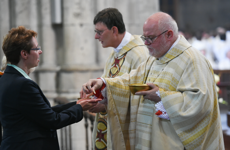 Cardinal Rainer Maria Woelki of Cologne, Germany, and Cardinal Reinhard Marx of Munich and Freising distribute Communion during Cardinal Woelki's installation Mass at the cathedral in Cologne on Sept. 20, 2014. (CNS photo/Jorg Loeffke, KNA)