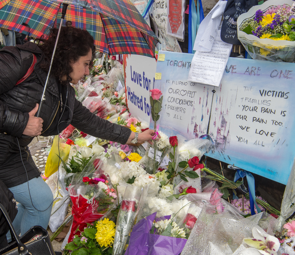 A woman places a flower at a makeshift memorial on April 25 near the Toronto sidewalk where 10 people were killed on April 23 after a van ran into them. (CNS photo/Michael Swan, The Catholic Register)