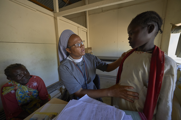 Precious Blood Sister Catherine Tukay examines a young patient in the Catholic clinic in Kauda, a village in the Nuba Mountains of Sudan, April 30. (CNS photo/Paul Jeffrey)