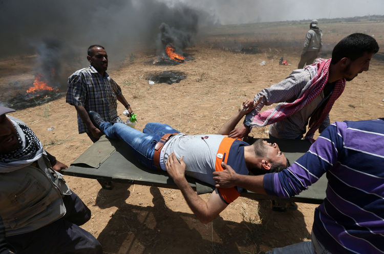 A wounded Palestinian is evacuated at the Israel-Gaza border during a protest against the U.S. embassy move to Jerusalem May 14. (CNS photo/Ibraheem Abu Mustafa, Reuters)