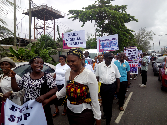 Nigerians carry placards during a May 22 protest in Lagos against the killing of innocent citizens, presumably by herdsmen, in some parts of the country. Catholics marched in various cities around the country. (CNS photo/Peter Dada)