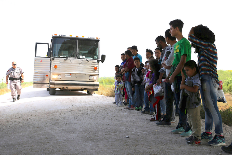 Immigrants turn themselves in to Border Patrol agents on April 2 after illegally crossing the border from Mexico into the U.S., and wait to be transported to processing center near McAllen, Tex. (CNS photo/Loren Elliott, Reuters)