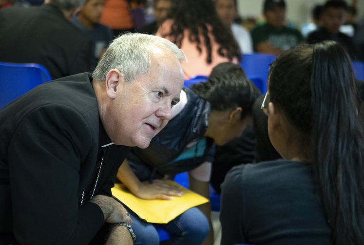 Bishop Joseph C. Bambera of Scranton, Pa., talks to an immigrant woman, recently released from U.S. custody, on July 1 at a Catholic Charities center in McAllen, Tex., as part of a fact-finding trip to the border by a delegation of U.S. bishops. (CNS photo/Chaz Muth)