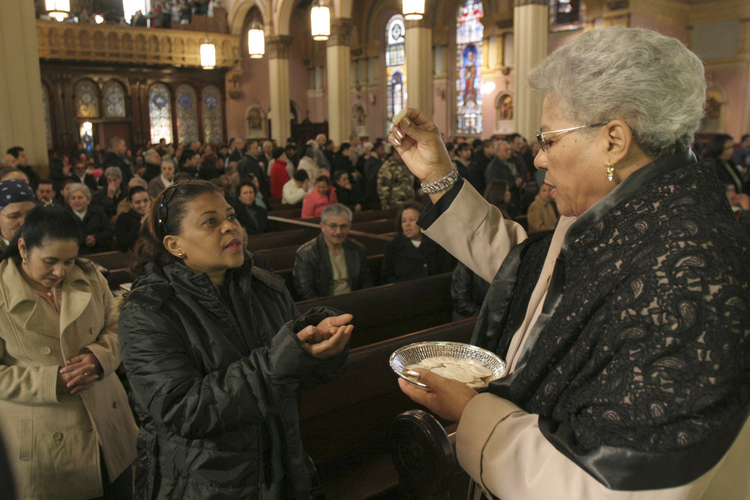 An extraordinary minister of the holy Eucharist distributes Communion during Mass at Transfiguration Church in the Williamsburg section of Brooklyn, N.Y.  (CNS photo/Gregory A. Shemitz)