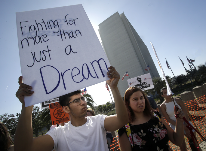 "A protester holds a sign that reads ""Fighting for more than just a Dream,"" as he joined Dreamers and hundreds of demonstrators calling for Deferred Action for Childhood Arrivals, or DACA, in early February outside the Federal Building in Los Angeles. CNS photo/Mike Nelson, EPA)"