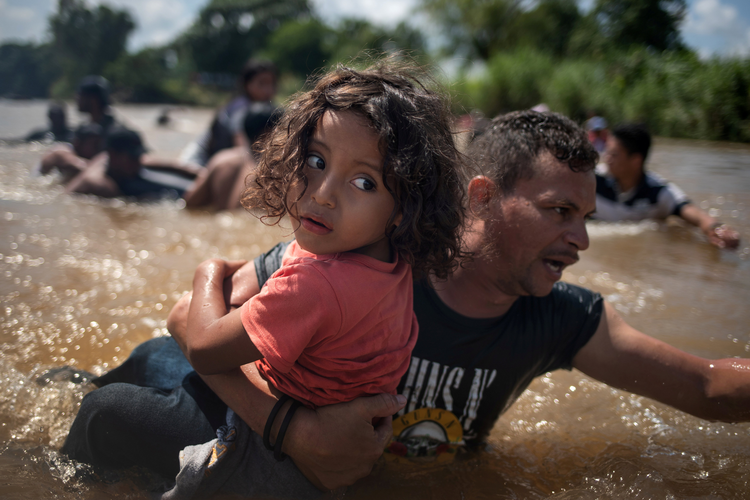 A man, part of a caravan of migrants from Central America to the United States, carries a girl Oct. 29 through the Suchiate River into Mexico from Guatemala. (CNS photo/Adrees Latif, Reuters)