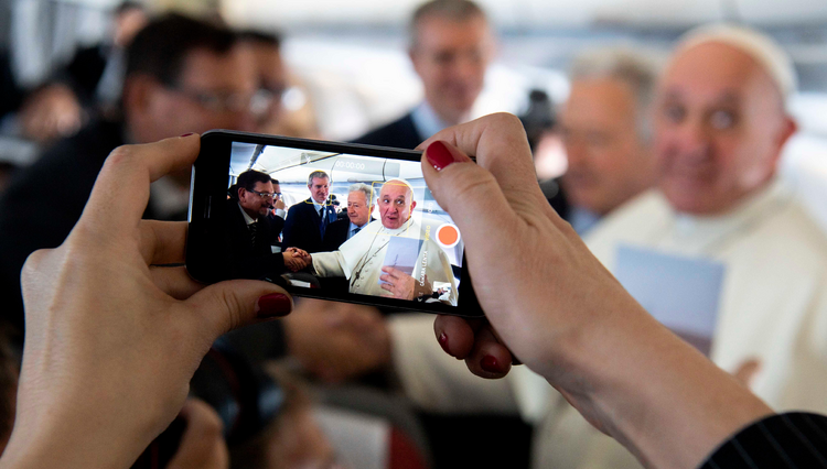 A journalist takes a cell phone photo of Pope Francis Jan. 23, 2019, aboard his flight from Rome to Panama for World Youth Day. (CNS photo/Vatican Media)