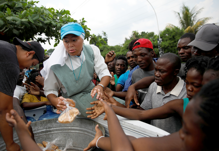A member of the Missionaries of the Risen Christ provides migrants with food in Tapachula, Mexico, May 11, 2019. Some African and Haitian migrants have been stranded in southern Mexico for two months. (CNS photo/Andres Martinez Casares, Reuters)