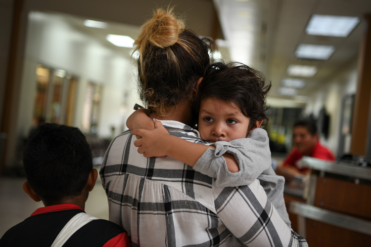 A Honduran asylum seeker released from detention holds her son while waiting at a bus depot in McAllen, Texas, on May 19. (CNS photo/Loren Elliott, Reuters)