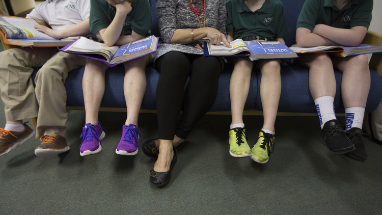 A teacher at Holy Name of Jesus Catholic School in Henderson, Ky., helps third-grade students with a reading lesson on March 28, 2019. A new document from the Vatican Congregation on Education states that Catholic schools and parents must help teach children that gender is fixed from birth. (CNS photo/Tyler Orsburn)