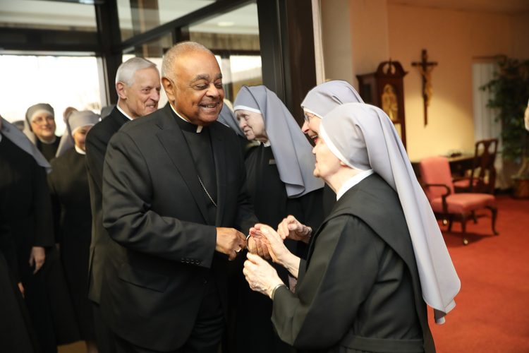 Archbishop Wilton D. Gregory greets a Little Sister of the Poor at the Jeanne Jugan Residence the order operates for the elderly poor in Washington April 5, 2019. (CNS photo/Jaclyn Lippelmann, Catholic Standard)