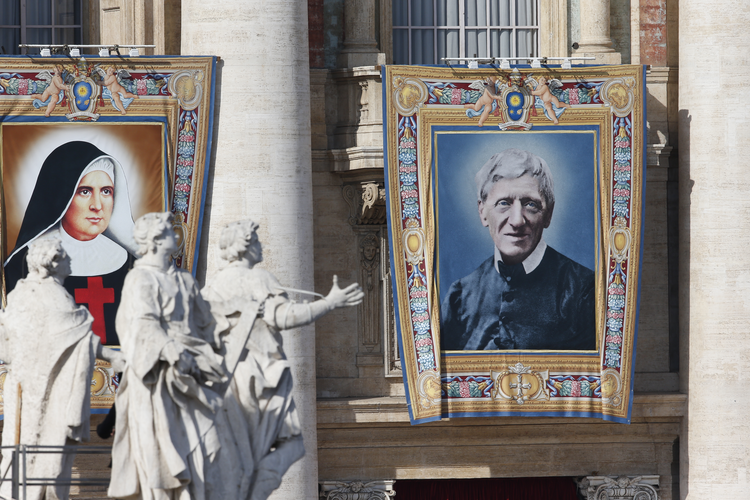 Banners showing new Sts. Giuseppina Vannini and John Henry Newman hang from the facade of St. Peter's Basilica as Pope Francis celebrates the canonization Mass for five new saints in St. Peter's Square at the Vatican Oct. 13, 2019. (CNS photo/Paul Haring)