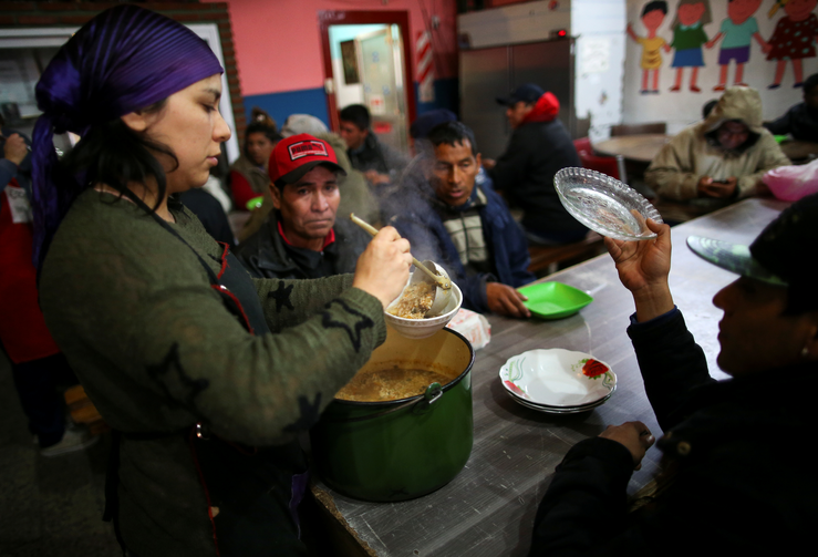 A volunteer serves a meal at a soup kitchen in Buenos Aires, Argentina, Oct. 4, 2019. Resolving the global crises of world hunger and malnutrition demands a shift away from a distorted approach to food and toward healthier lifestyles and just economic practices, Pope Francis said in an Oct. 16 message. (CNS photo/Agustin Marcarian, Reuters)
