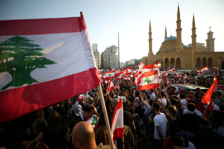 Image: Demonstrators near Al-Amin mosque in Beirut carry national flags during an anti-government protest Oct. 20, 2019. Fueled by economic insecurity and deteriorating living conditions, protests were sparked by government plans to impose new taxes. (CNS photo/Ali Hashisho, Reuters)
