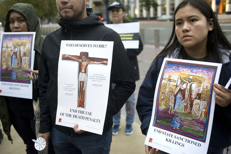 People hold signs during a candlelight prayer vigil Dec. 8, 2019, held to oppose the Trump administration's plan to reinstate the federal death penalty. (CNS photo/David Maung)
