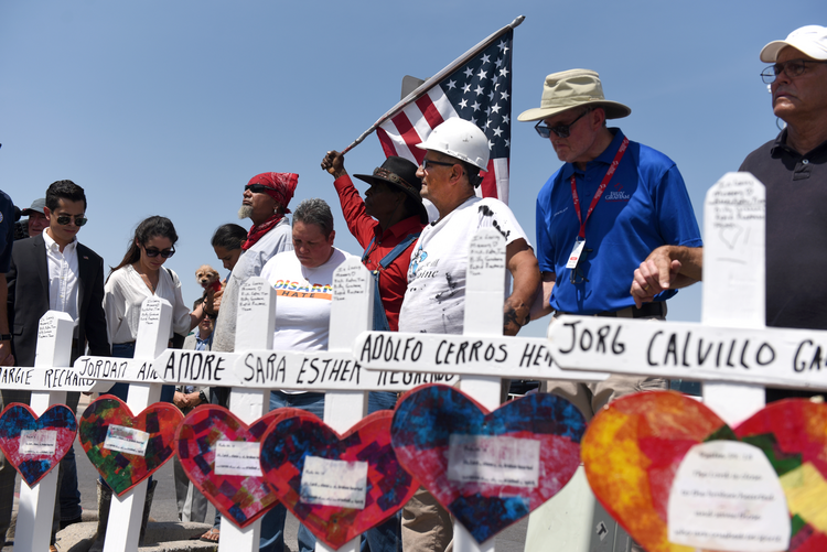 People hold hands in prayer Aug. 5, 2019, next to crosses in honor of victims of a mass shooting at a Walmart store in El Paso, Texas, two days earlier. A year after the deadly shooting, El Paso Bishop Mark J. Seitz has announced the formation of a group to address racism as a way to honor the victims. (CNS photo/Callaghan O'Hare, Reuters)