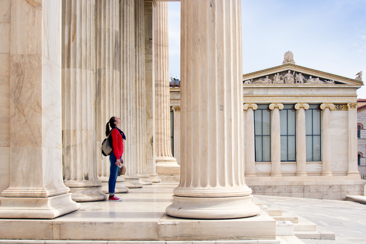 Surveying the world from beneath the columns of the Academy of Athens, in Greece. (iStock/sarra22)