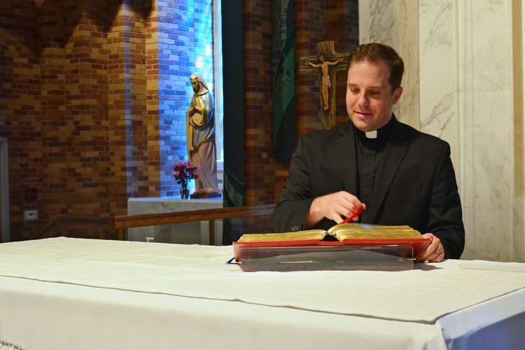 Rev. Matthew Hood thumbs through a missal at the altar of St. Lawrence Parish in Utica, Mich., on Aug. 21, 2020. Finding out he wasn't a priest was a painful realization, but it came with the grace of knowing God's providence, he said. (CNS photo/Michael Stechschulte, Detroit Catholic)
