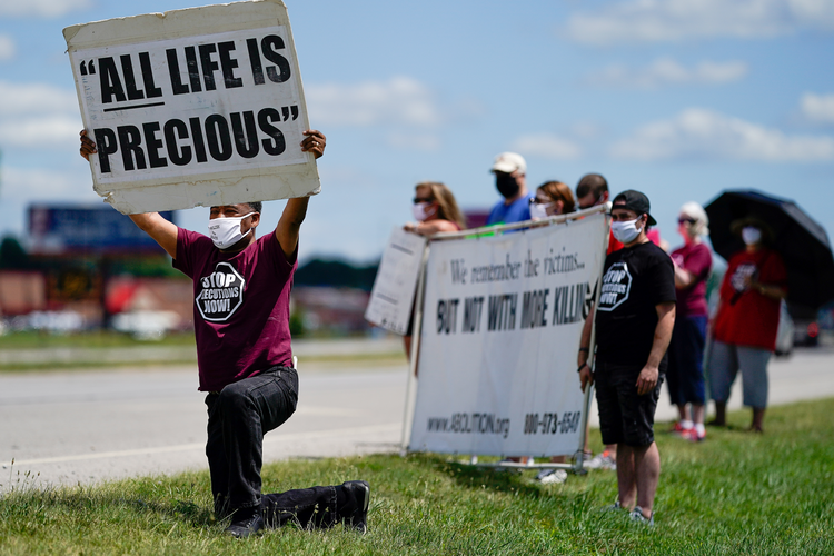 Demonstrators are seen near the Federal Correctional Complex in Terre Haute, Ind., to show their opposition to the death penalty July 13, 2020. (CNS photo/Bryan Woolston, Reuters)