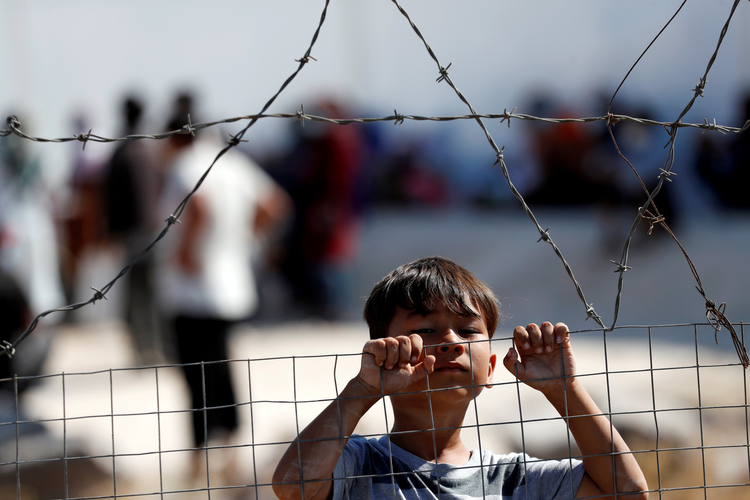 A displaced child from the Moria refugee camp looks over a fence inside a new temporary camp on the Greek island of Lesbos Sept. 23, 2020. (CNS photo/Yara Nardi, Reuters)