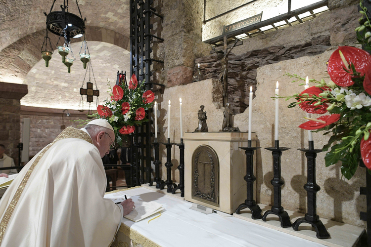 "Pope Francis signs his new encyclical, ""Fratelli Tutti, on Fraternity and Social Friendship"" after celebrating Mass at the Basilica of St. Francis in Assisi, Italy, Oct. 3, 2020. (CNS photo/Vatican Media)"