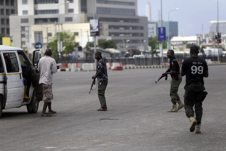 Police officers stop and search a bus carrying passengers around Lekki toll gate in Lagos Friday, Oct. 23, 2020. Resentment lingered with the smell of charred tires Friday as Nigeria's streets were relatively calm after days of protests over police abuses, while authorities gave little acknowledgement to reports of the military killing at least 12 peaceful demonstrators earlier this week. (AP Photo/Sunday Alamba)