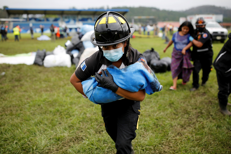 A firefighter carries a baby rescued along with her mother from an area affected by mudslides in San Cristobal Verapaz, Guatemala, Nov. 7, 2020, caused by the remains of Hurricane Eta. (CNS photo/Luis Echeverria, Reuters)
