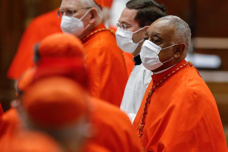 """20201128T1100 POPE CARDINALS CONSISTORY 1010078%20%282%29.JPG.JPG VATICAN CITY (CNS) — One by one 11 senior churchmen, including two U.S. citizens — Cardinals Wilton D. Gregory of Washington and Silvano M. Tomasi, a former Vatican diplomat — knelt before Pope Francis to receive their red hats, a cardinal's ring and a scroll formally declaring their new status and assigning them a """"titular"""" church in Rome."""