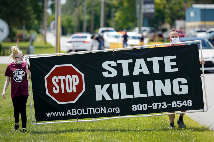 In July demonstrators show their opposition to the death penalty outside the Federal Correctional Complex in Terre Haute, Ind., where federal executions are conducted. (CNS photo/Bryan Woolston, Reuters)