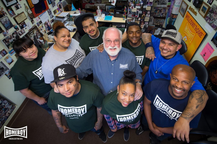 Jesuit Father Greg Boyle, founder of Homeboy Industries, poses for a photo with trainees in this undated photo