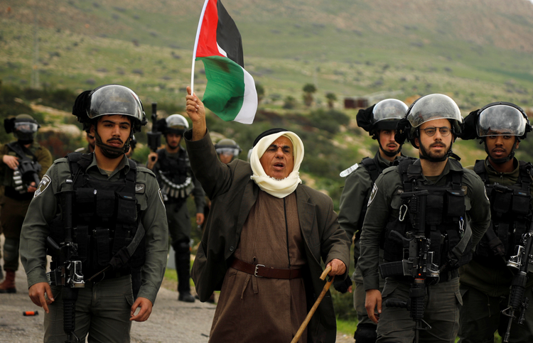 A demonstrator holding a Palestinian flag stands amid Israeli border police during a protest against Israeli settlements and U.S. President Donald Trump's Middle East peace plan. The protest was in the Jordan Valley, part of the Israeli-occupied West Bank, Feb. 25, 2020. (CNS photo/Raneen Sawafta, Reuters)