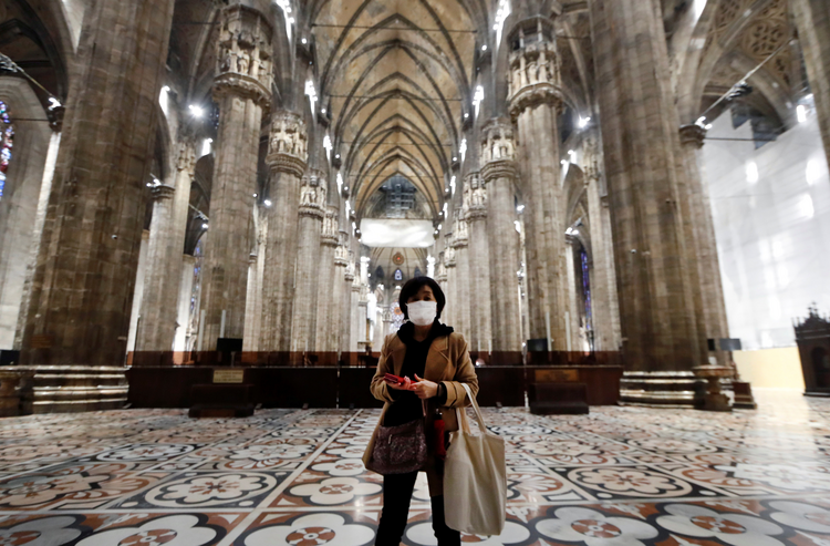 "A tourist wearing a protective mask visits Milan's famed cathedral, commonly referred to as the ""Duomo,"" as it reopened to the public March 2, 2020, for the first time since the coronavirus outbreak. (CNS photo/Yara Nardi, Reuters)"
