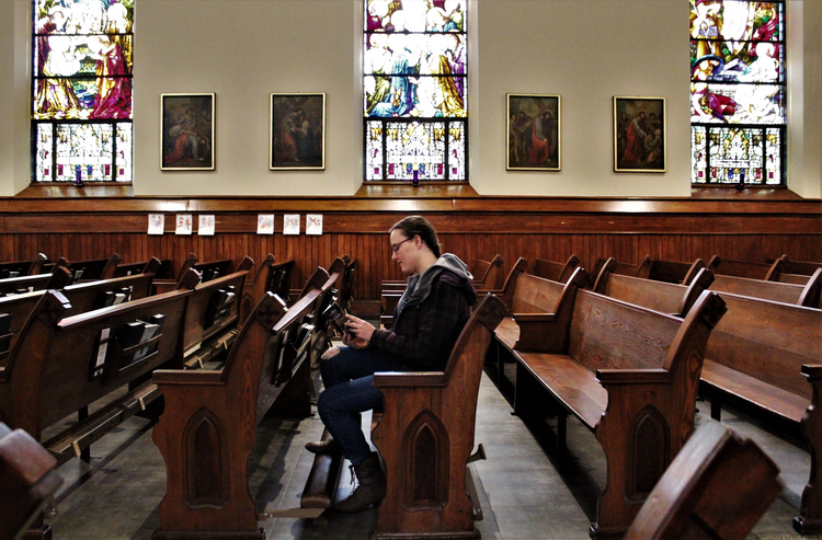 A woman reads a prayer book in the sanctuary of St. Mary Church in Appleton, Wis., on March 18,. Bishop David L. Ricken of Green Bay announced on March 17 that all public Masses in the diocese are suspended for the next four to eight weeks due to the coronavirus pandemic. (CNS photo/Brad Birkholz)