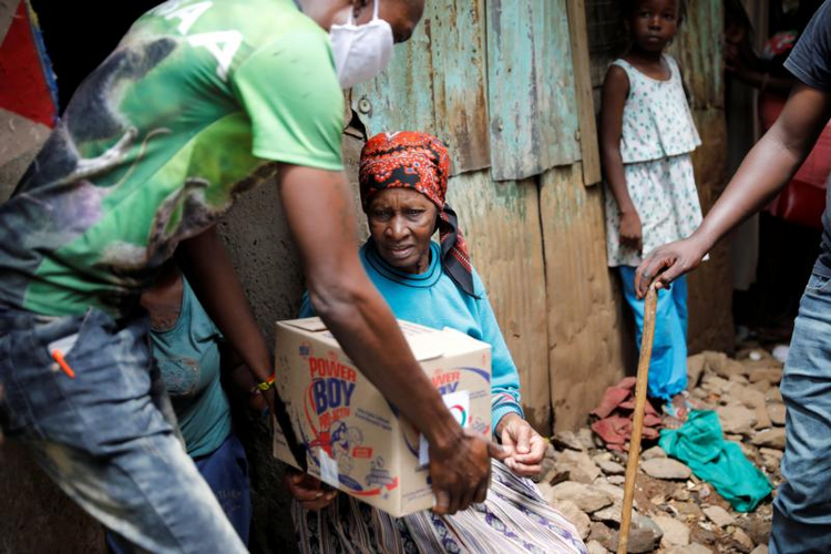 An elderly woman receives a box of food donations given by an aid group to people in need in a poor section of Nairobi, Kenya, April 14, 2020, during the coronavirus pandemic. U.S.-based aid groups are providing funding and other support to communities most vulnerable to COVID-19 around globe. (CNS photo/Baz Ratner, Reuters)