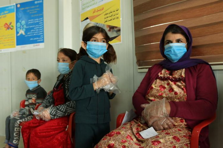 Image: Displaced women and children wearing protective masks wait in the medical center of a camp in Dahuk, Iraq, March 7, 2020, during the COVID-19 pandemic. (CNS photo/Ari Jalal, Reuters)