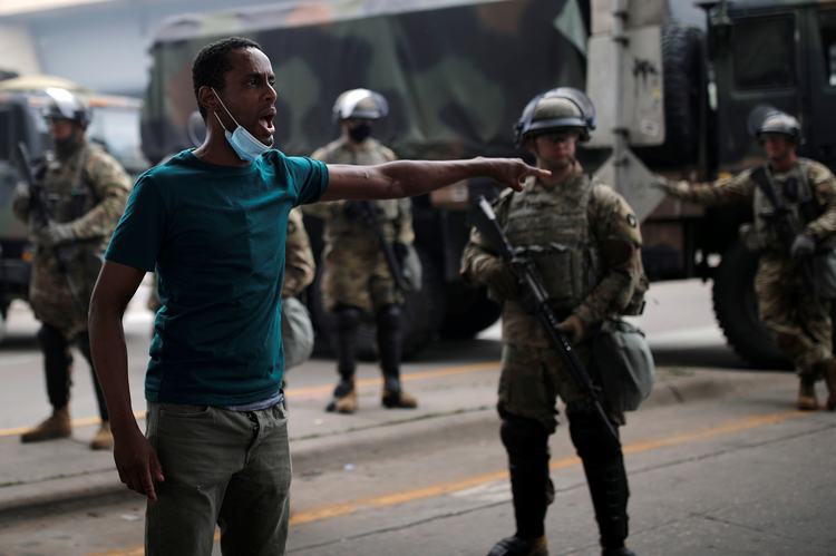 A protestor in Minneapolis gestures near National Guard members on May 29, 2020, arriving in the aftermath of a protest over the death of George Floyd, an African American, while in the custody of a white police officer. (CNS photo/Carlos Barria, Reuters)