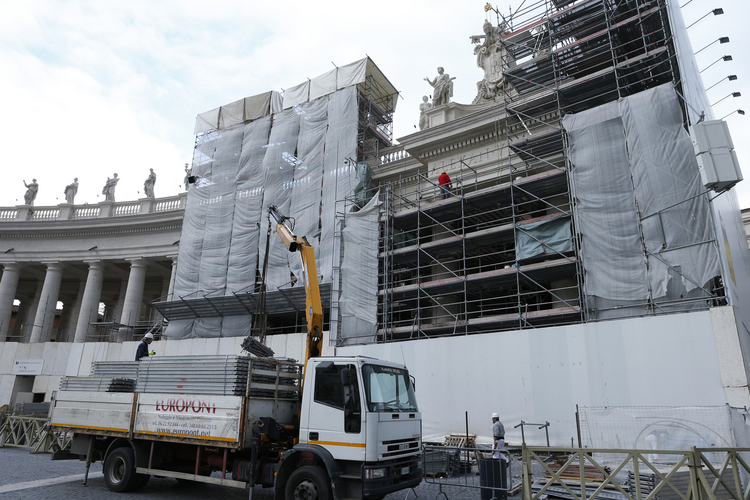 Vatican workers remove scaffolding from the final restored section of the colonnade in St. Peter's Square at the Vatican in this January 2014 file photo. Pope Francis issued a new set of laws June 1, 2020, that govern the awarding of contracts for goods and services provided by outside vendors. (CNS photo/Paul Haring)