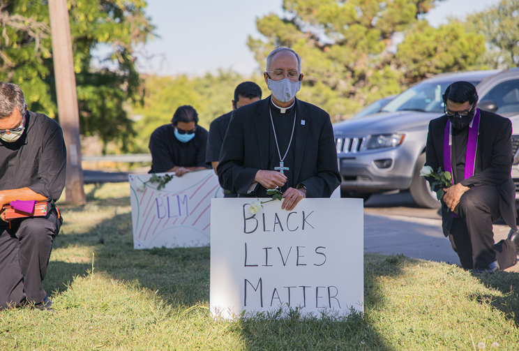 Bishop Mark J. Seitz of the Diocese of El Paso, Texas, kneels at El Paso's Memorial Park holding a Black Lives Matter sign June 1, 2020. Bishop Seitz and other clergy from the Diocese of El Paso, prayed and kneeled for eight minutes, the time George Floyd, an unarmed black man, was said to have spent under a police officer's knee before becoming unconscious and later dying May 25, 2020. (CNS photo/Fernie Ceniceros, courtesy Diocese of El Paso)