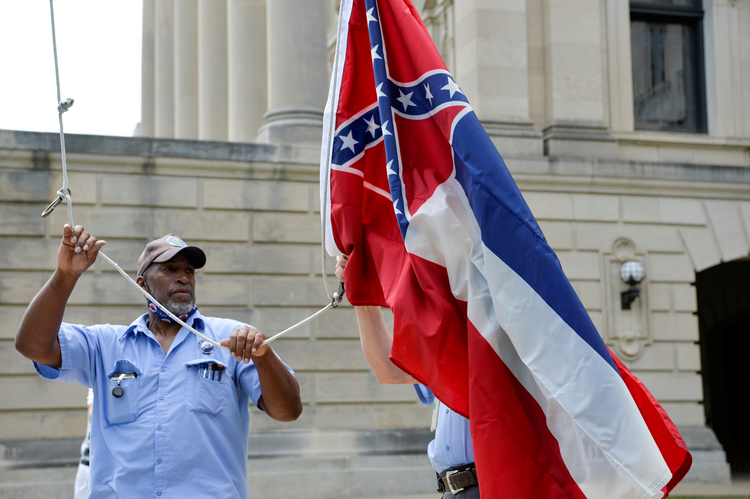 An employee at the Mississippi Capitol raises and lowers a commemorative state flag June 30, 2020, a flag that is purchased by people from all around the world. Hours later, Mississippi Gov. Tate Reeves signed a bill into law to replace the current state flag, which includes the Confederate emblem. (CNS photo/Suzi Altman, Reuters)