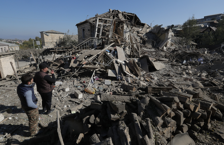 The genocide of Christians in the Middle East continues to this day, as seen in Azerbaijan's occupation of Nagorno-Karabakh, a disputed region with an Armenian majority. In this photo, men look at the ruins of a house in the city of Stepanakert on Oct. 17, 2020. (CNS photo/Reuters)