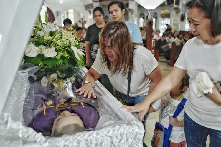 Mourners grieve by the casket of Father Richmond Nilo on June 11 n Zaragoza, Nueva Ecija, Philippines. Photo by Ezra Acayan.
