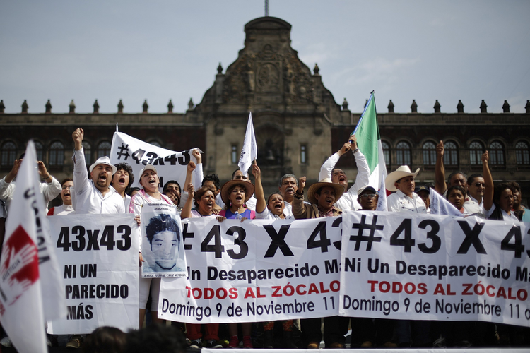 People carry banners and flags in Mexico City Nov. 9, as they take part in a protest to demand more information about the 43 missing students. They marched 112 miles from Iguala. (CNS photo/Tomas Bravo, Reuters)
