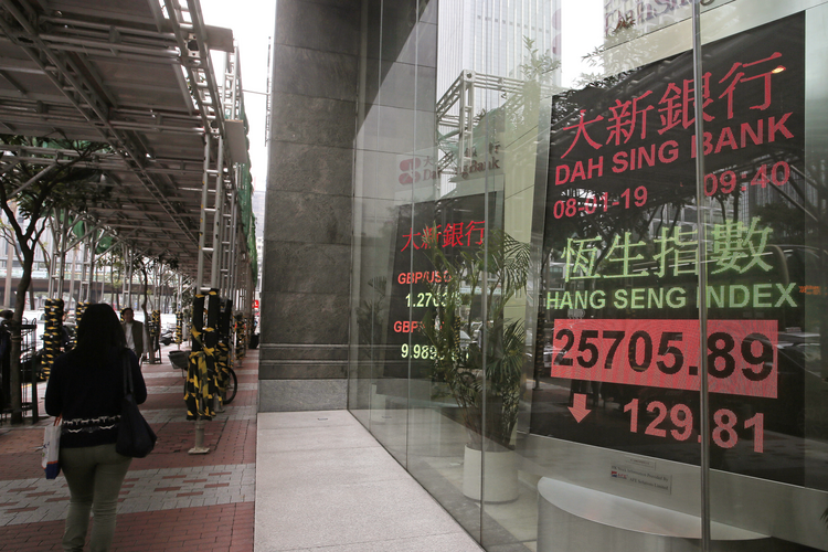 People walk past an electronic board showing Hong Kong share index outside a local bank in Hong Kong Monday, Jan. 8, 2019. (AP Photo/Vincent Yu)