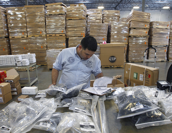 Claudio Montes checks a shipping manifest for U.S. manufactured parts heading to assembly plants in Mexico at Freight Dispatch Service Agency LTD in Pharr, Texas in June 2017. The freight service ships parts between the U.S. and Mexico that pass through the border freely due to the North American Free Trade Agreement. (Nathan Lambrecht/The Monitor via AP, File)