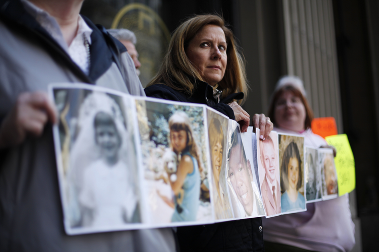 In this March 29, 2011, file photo, Barbara Blaine, President of Survivors Network of those Abused by Priests (SNAP), displays childhood photographs of adults who say they were sexually abused, during a news conference in Philadelphia. Barbara Blaine, the founder and former president of the Survivors Network of those Abused by Priests, has died. The organization known as SNAP announced on its Facebook page that Blaine died Sunday, Sept. 24, 2017, following a recent cardiac event. She was 61. (AP Photo/Matt