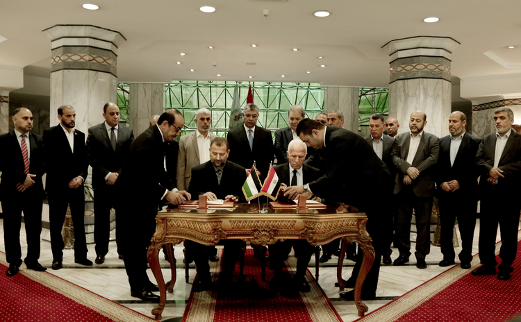 Senior Fatah official Azzam al-Ahmad, center right, and Hamas' representative, Saleh al-Arouri, center left, sign a reconciliation agreement during a press conference at the Egyptian intelligence complex in Cairo, Egypt, Thursday, Oct. 12, 2017. Thursday's signing came after two days of negotiations in the Egyptian capital on the governing of the Gaza Strip as part of the most serious effort to date to end the 10 year rift between the rival Palestinian groups. (AP Photo/Nariman El-Mofty)