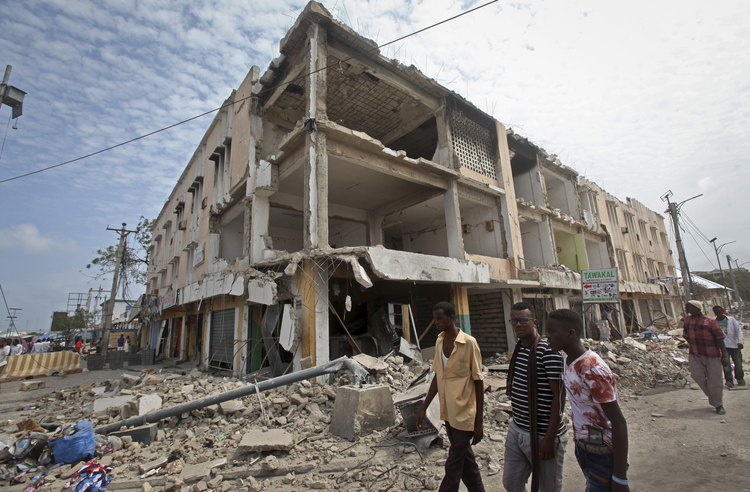 Men walk near destroyed buildings as thousands of Somalis gathered to pray at the site of the country's deadliest attack and to mourn hundreds of victims at the site of the attack in Mogadishu, Somalia, on Oct. 20. (AP Photo/Farah Abdi Warsameh)