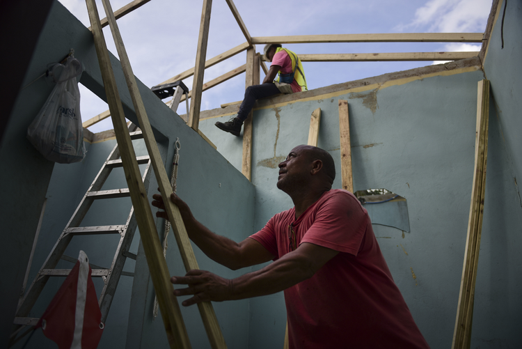 In this Nov. 15 photo, Pedro Deschamps helps workers hired by FEMA to carry out the installation of a temporary awning roof at his house, which suffered damage during Hurricane Maria, in San Juan, Puerto Rico. (AP Photo/Carlos Giusti)